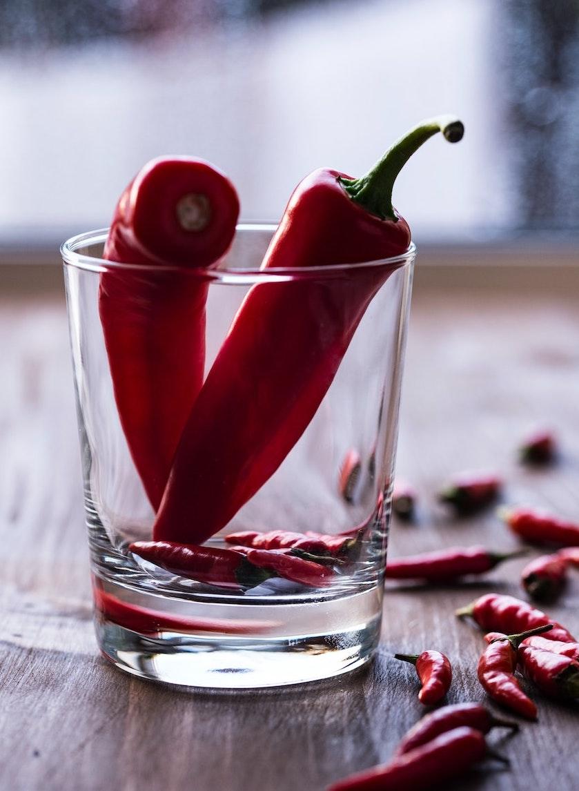 κόκκινες πιπεριες σε γυαλινο ποτηρι