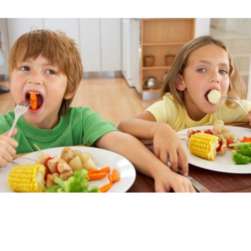 αγόρι και κορίτσι που τρώνε σε τραπέζι