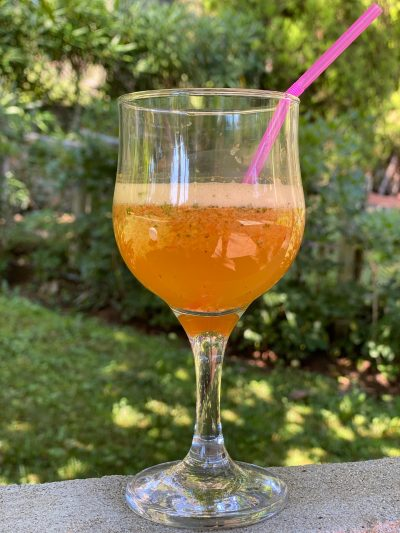 κολωνάτο ποτήρι με πορτοκαλί χυμό και καλαμάκι